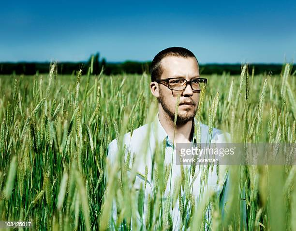 Adult male with glasses standing in a wheat field