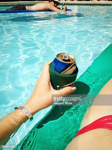 Adult man and woman enjoy a cold beer while floating on rafts in a backyard pool in Brookfield Wisconsin