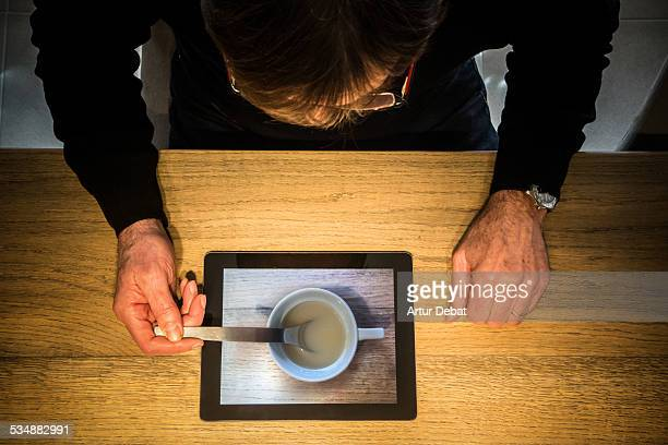 Adult man eating from Ipad with optical illusion.
