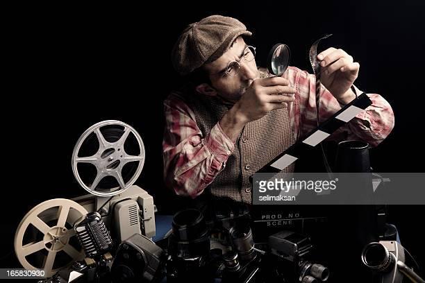 Adulto uomo che tiene un Cinema Film e il controllo con la lente d'ingrandimento