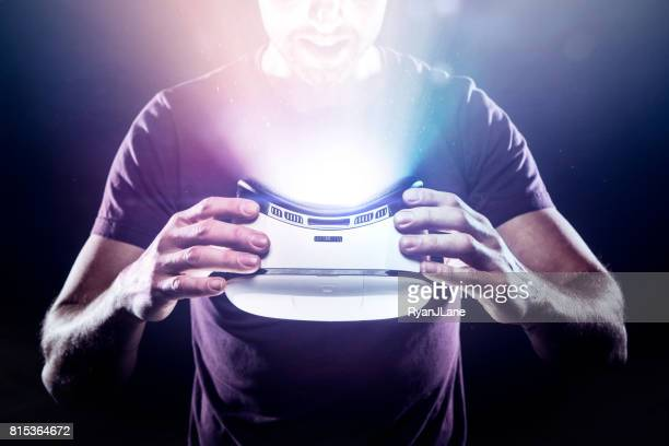 Adult Man Holding Glowing VR Headset