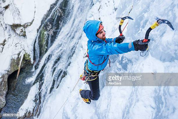 Adult man ice climbing a frozen cascade