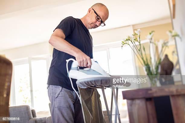 Adult man ironing his shirt at home