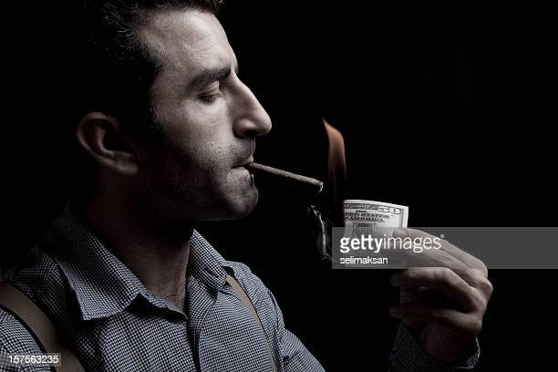 Adult man lighting up a cigarette with burnt dollar bill