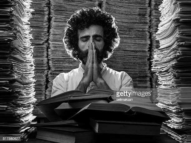 Adult man reading praying and thinking in library