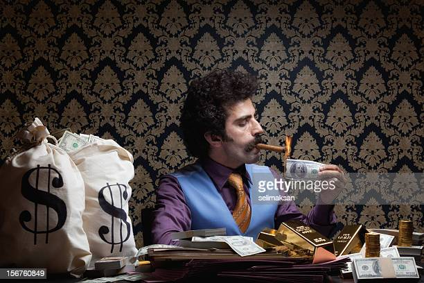 Adult man sitting lighting cigar with burnt dollar bill
