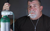 A adult man dangerously smokes a cigarette while wearing an oxygen cannula while holding on to an oxygen gas tank.