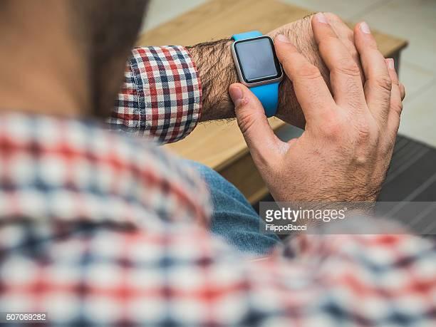 Anziani uomo utilizzando il tecnologico orologio