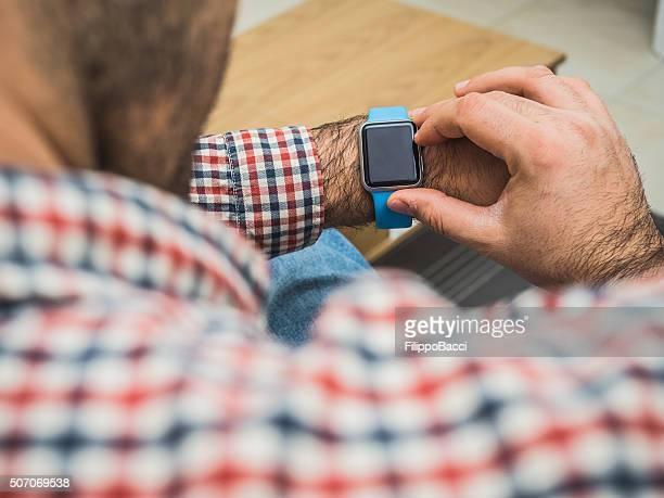 Erwachsener Mann mit seiner technischen Uhr