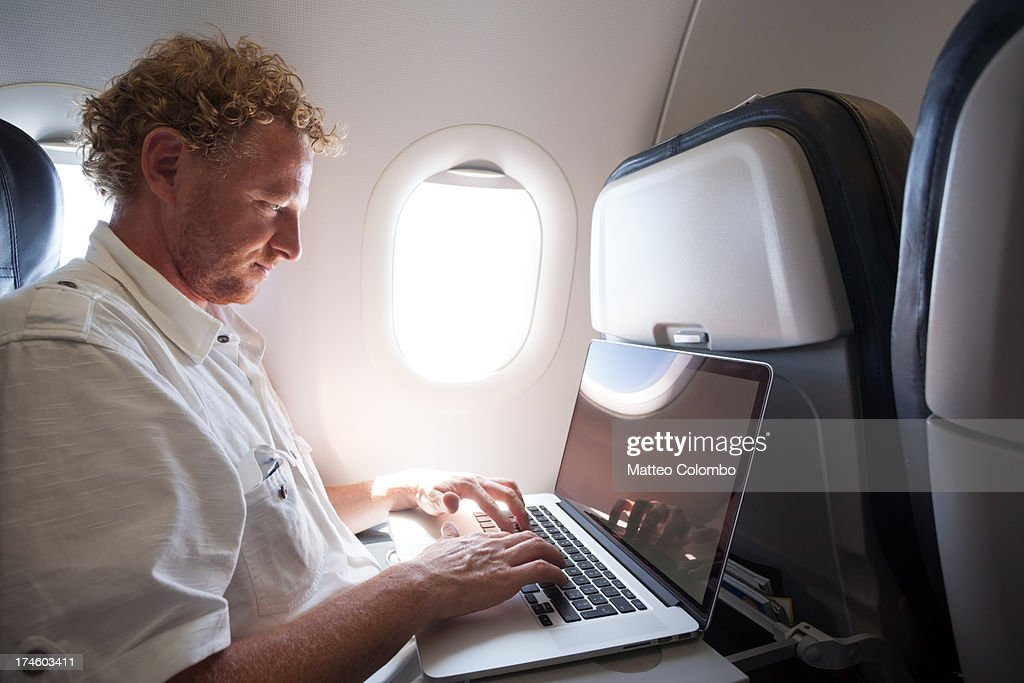 Adult man using laptop on the plane : Stock Photo