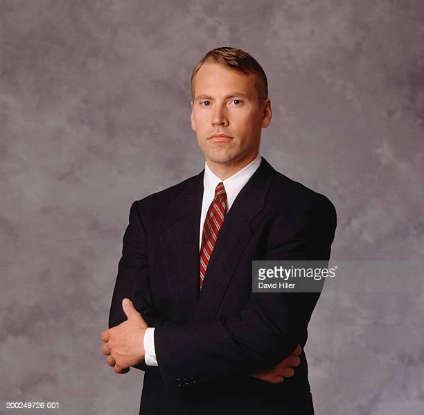 Adult man wearing suit, arms crossed