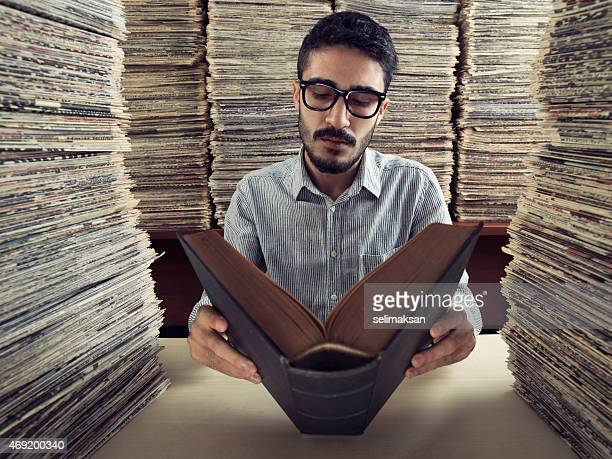 Adult man with dark hair reading book in media archive