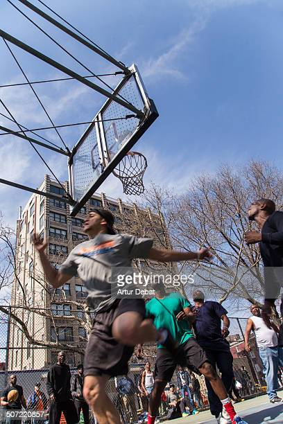 Adult men playing at the basketball court in the streets on New York City in a work break with the cityscape