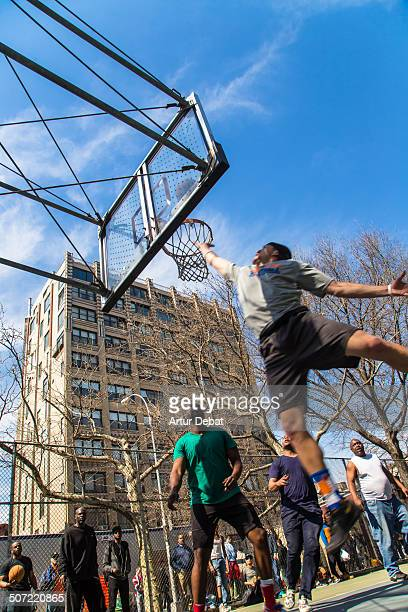 Adult men playing at the basketball court in the streets on New York City with below view and cityscape of the city