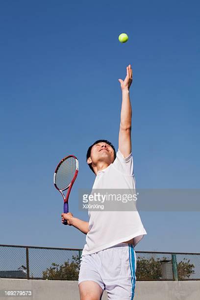Adult men serving the tennis ball