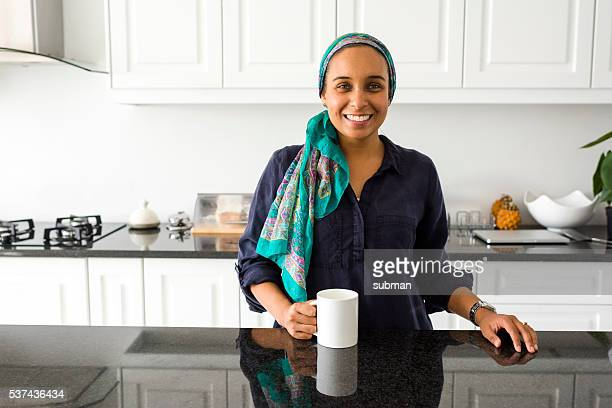 Adult Muslim Woman Drinking Coffee In Her Kitchen