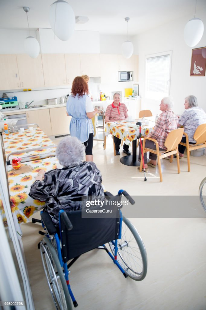 Adult Senior Socializing In The Dining Room Of The Care Center : Stock-Foto