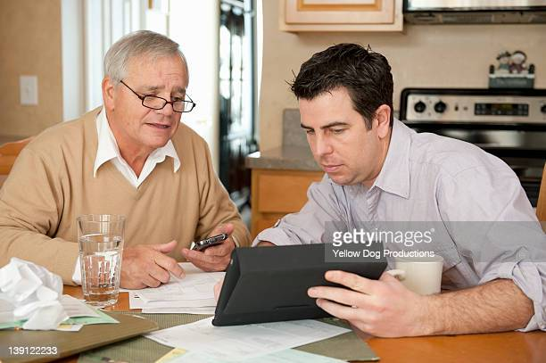 Adult Son Helping Senior Father with Finances