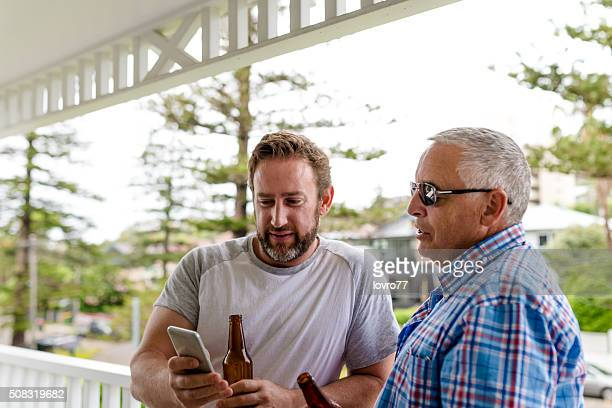 Adult son with his father with mobile phone