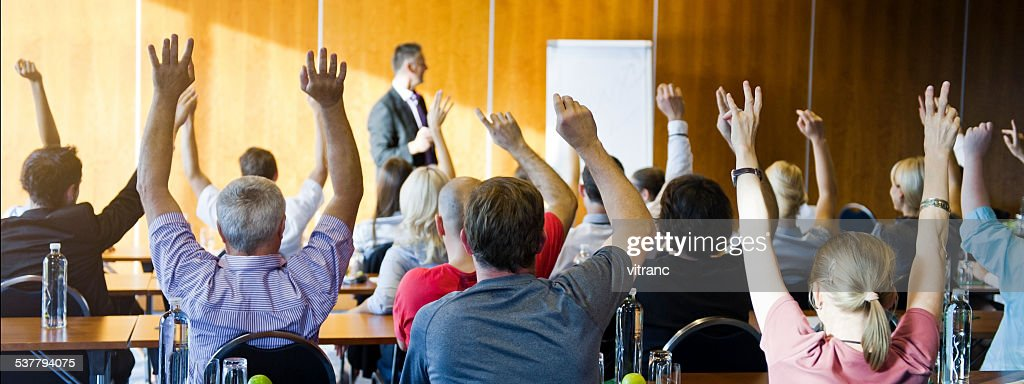 Adult students raising hands on seminar : Stock Photo