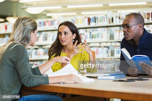 Adult students studying  together in library