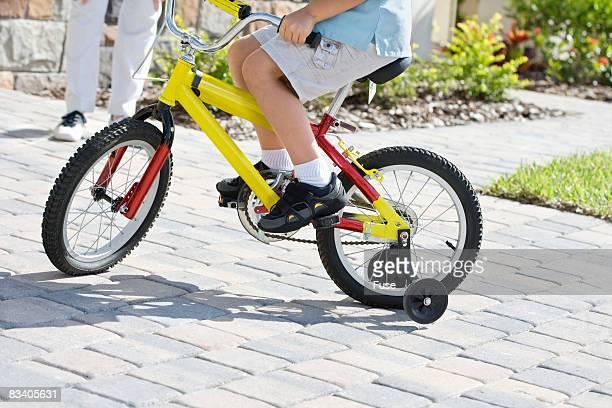 Adult Watching Boy Biking in Driveway