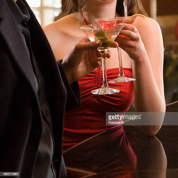 adult woman and man toasting martinis.