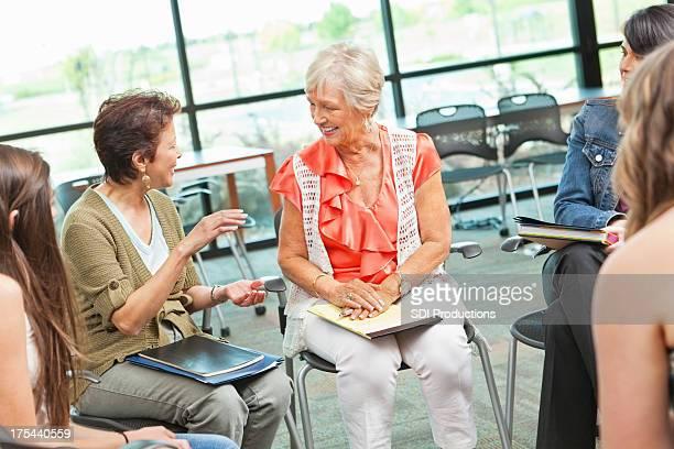 Erwachsene Frau erklärt etwas zu Gruppe