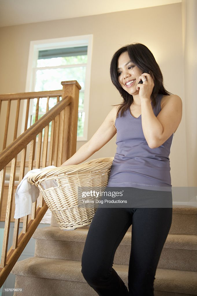 Adult woman on phone while carrying laundry  : Stock Photo