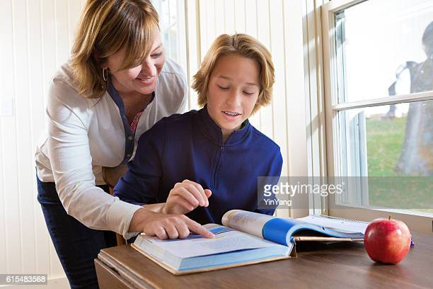 Adult Woman Teacher or Mother Helping Teen Studying and Homework