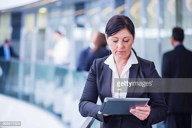 Adult woman using digital tablet in a modern office hallway