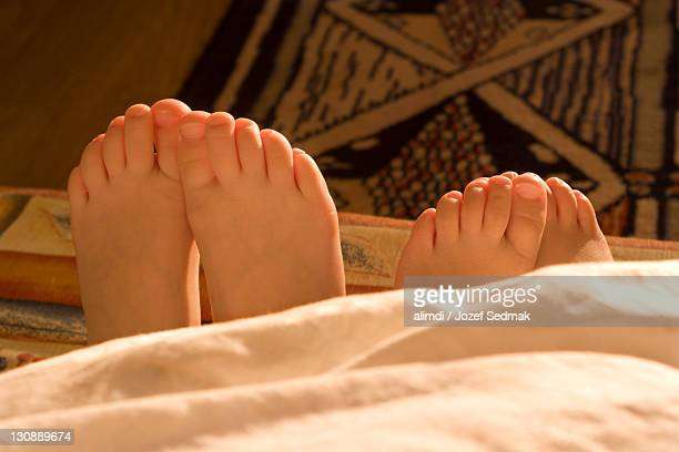 Adult woman's and child's feet peeking out from under a blanket
