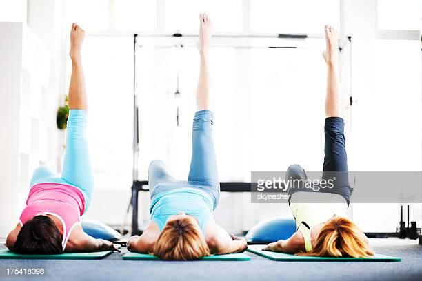 Adult women doing stretching exercises on Pilates class.