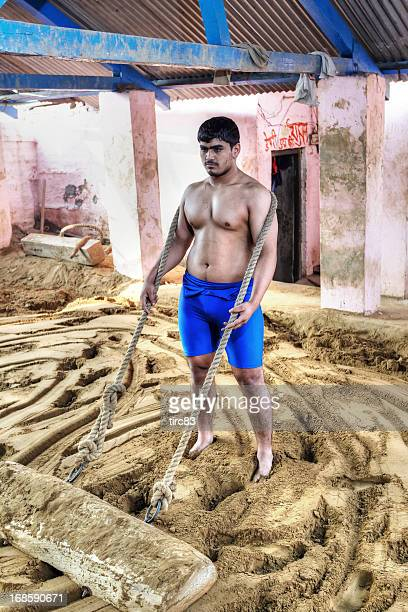 Adult wrestler dragging concrete block on sand