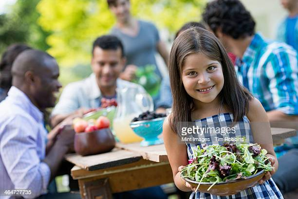 Adults and children around a table in a garden. A child holding a bowl of salad.