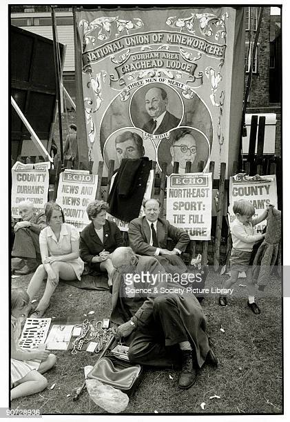 Adults and children sitting by National Union of Mineworkers' banner Photograph taken at Durham miners' gala County Durham Photographer Tony RayJones...