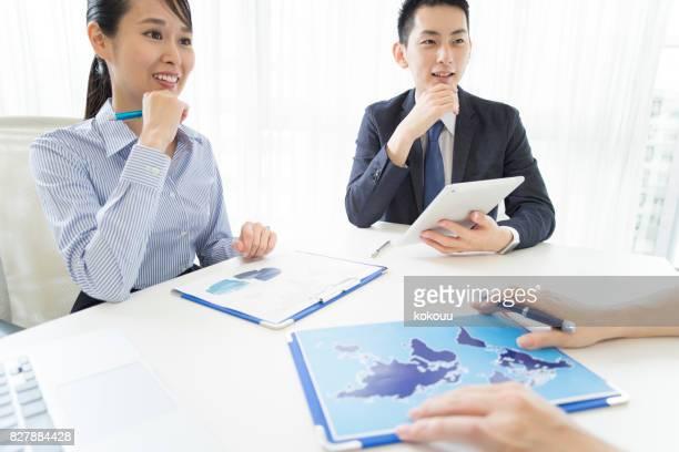 大人は世界地図上の資料を見ているし、話しています。