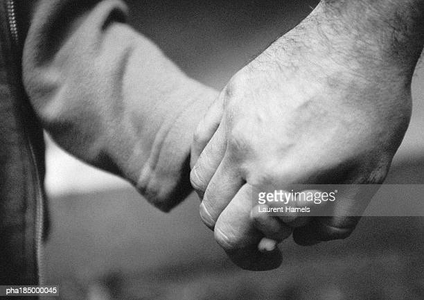 Adult's hand holding child's hand, close-up, b&w
