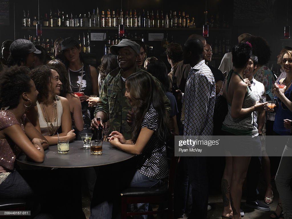 Adults talking and drinking cocktails in nightclub : Stock Photo