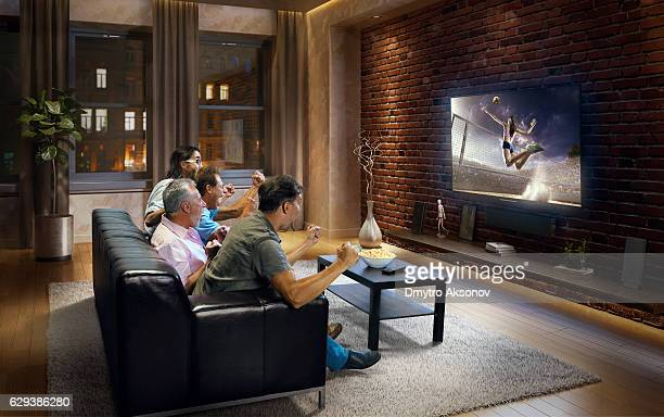 Adults watching Volleyball game at home