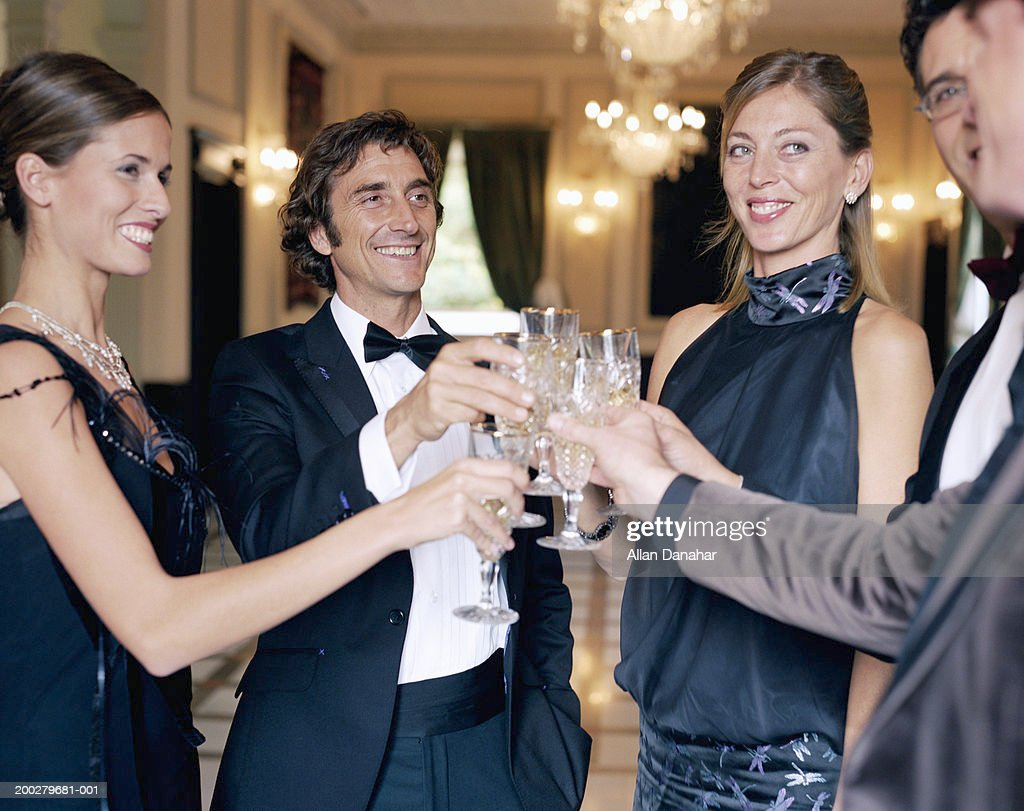 Adults wearing formal attire, toasting champagne glasses