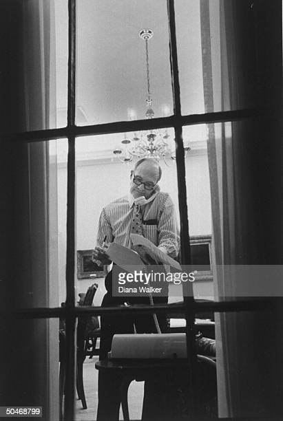 NSC Adv Brent Scowcroft in shirtsleeves talking on telephone as he goes over some papers while standing in his WH office at night as seen through...