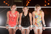 Winning Smiles From Three Teenaged Gymnasts Pose On Uneven Bars