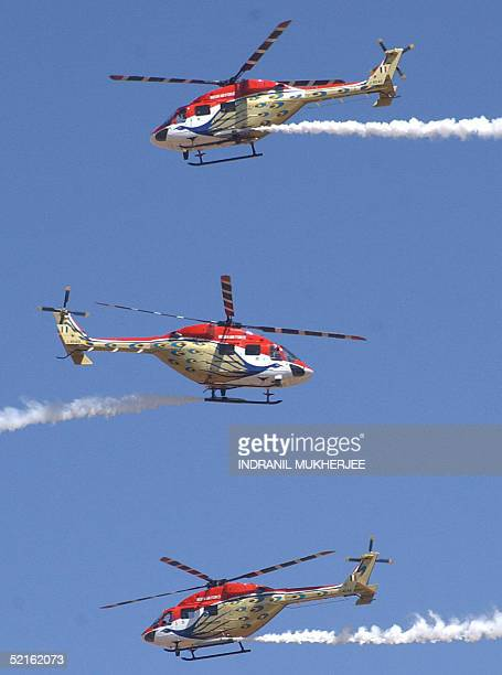 Advanced Light Helicopters of the Indian Air Force's Sarang aerobatics team perform during the inaugural function of the Aero India 2005 airshow at...