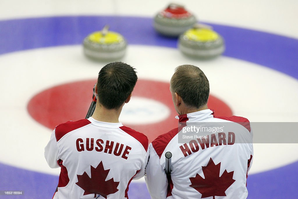 ADVANCES---02/22/06---Brad Gushue and Russ Howard discuss a shot as their rink advances to the Gold Medal game after beating USA 11-5 at the Pinerolo Palaghiaccio at the Torino 2006 XX Winter Olympics hosted by Turin, Italy , February 22, 2006.