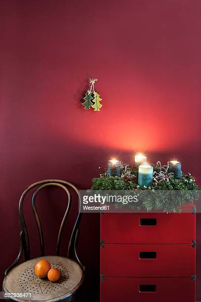 Advent wreath on sideboard at red wall