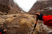First person point of view of a hiker holding his hiking poles, while trekking on Annapurna Range on Himalayas, Nepal