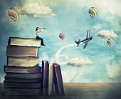 Surreal view as a young woman student stand on the top of a huge pile of books holding a spyglass looking far at horizon. Adventure concept, as airplane and hot air balloon fly out of the magic book.