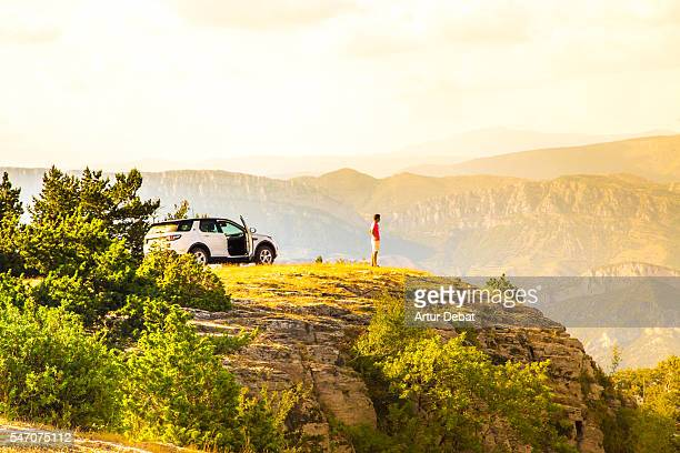 Adventure guy traveling around the Pyrenees mountains driving with suv car to the top of the mountains with nice views on sunset.