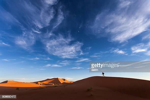 Adventure man walking on dunes in desert Sahara, Morocco, Africa